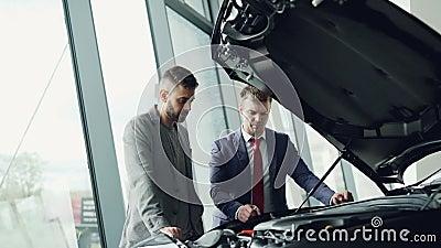 Опытный автодилер показывает новый двигатель клиента под раскрытым bonnet и говорит ему о качестве и характеристиках  видеоматериал