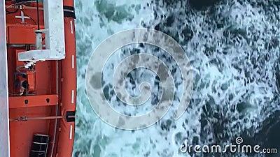 Оранжевый корабль, плывущий по холодно-голубым океанам, с волнами и пеной, видом на воздух видеоматериал