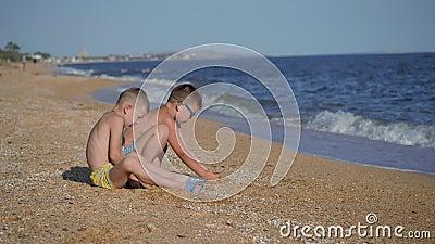 Отдых на море с детьми Мальчики бросают оболочку с песком Детские эмоции Мальчики бросают песок сток-видео