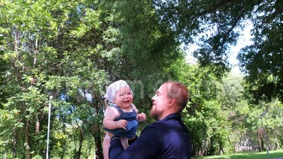 Отец бросает свою дочь в воздух и ловит в городском парке во время прогулки сток-видео