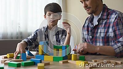Отец и серьезный сын играя с кубами игрушки, строя дом совместно, отдых видеоматериал
