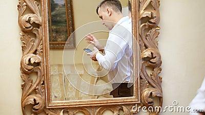 Отражение в зеркале красивый человек, бизнесмен в белой рубашке держит смартфон, мобильный телефон Молодая ванта видеоматериал