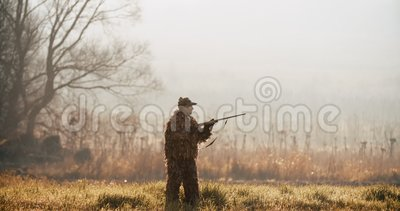 Охотник в оборудовании звероловства направляет цель с винтовкой в поле на туманное утро или солнечный вечер осени видеоматериал