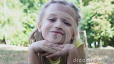Очаровательная улыбающаяся девушка, смотрящая камеру, трав парка, летний отдых, детство видеоматериал