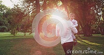 Очень милый мальчик со своим отцом, наслаждающийся временем, играющий очень счастливо и улыбаясь вместе в парке акции видеоматериалы