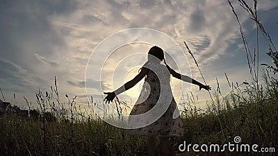 Один танц маленькой девочки в поле на времени захода солнца акции видеоматериалы