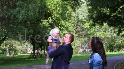 Папа бросает свою дочь в воздух и ловит в городском парке, мама стоит рядом с семьей видеоматериал