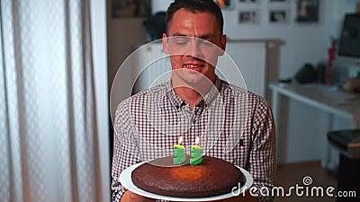Парень делает желание на свой день рождения Держать торт в руках сток-видео
