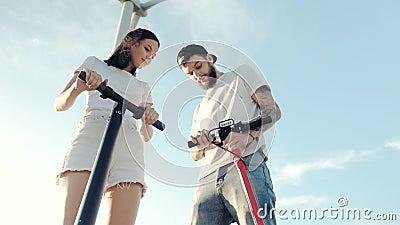 Парень показывает своей подруге управление электрическим скутером на фоне соседнего ветрогенератора видеоматериал