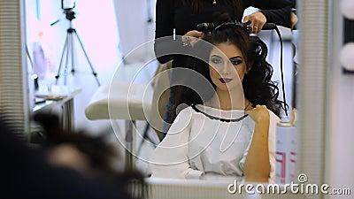 Парикмахер делает hairdress красивую девушку в салоне красоты сток-видео