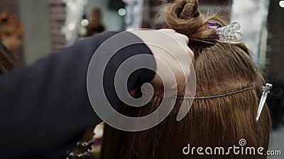 Парикмахер шьет искусственные волосы к первоклассной вещи Процесс расширения волос 4K акции видеоматериалы