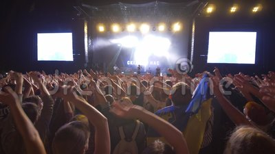 Партия утеса, почитатели толпы развевая руки на концерте живой музыки против яркого освещенного этапа с большими экранами вечером видеоматериал
