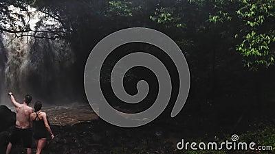 Пары в любов под водопадом в пещере нежность пар любовников сработанности ощупывания Отключение Бали tropics Путешествие Воздушна видеоматериал