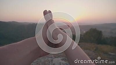 Пары держат руки на предпосылке захода солнца видеоматериал