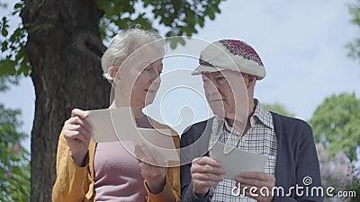 Пары портрета прелестные зрелые выглядя старыми фото вспоминая, что счастливые моменты сидели на стенде в парке adulteration сток-видео