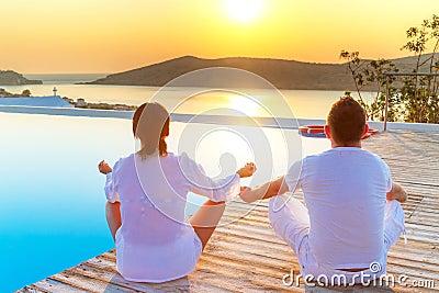 Пары meditating на восходе солнца