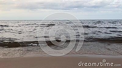 Пасмурный день берега озера хмурый Волны свертывают на песочном береге акции видеоматериалы