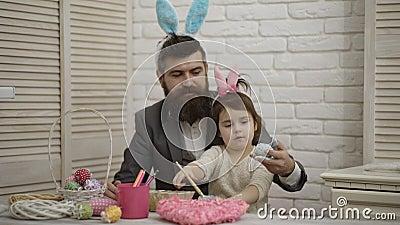 пасха счастливая Папа и его маленькая дочь совместно имеют потеху пока подготавливающ на праздники пасхи На таблице корзина видеоматериал