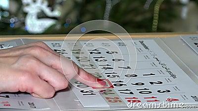 Палец нажимая бумажную отметку календаря пашет праздник рождества сток-видео