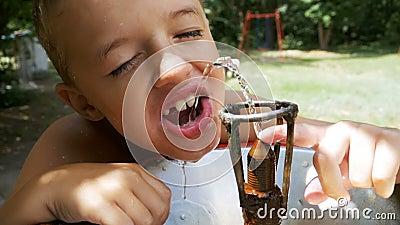 Питьевая вода счастливого мальчика смешная от выпивая фонтана на спортивной площадке в замедленном движении видеоматериал