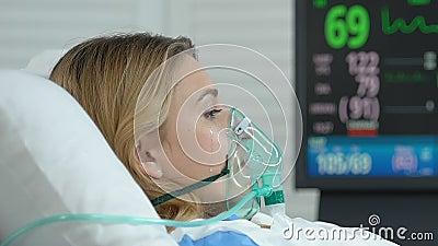 Плачущая женщина в кислородной маске, лежащая кровать, депрессия, страх болезни акции видеоматериалы
