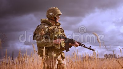 Подлинный солдат в военных одеждах и шлем стоя все еще и поворачивая вокруг с оружием в руках, потерянных в природе сток-видео