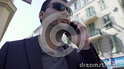 Подозрительный человек говоря над телефоном, член группы гангстера в улице города акции видеоматериалы