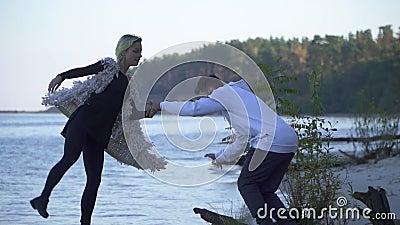 Подростки в танцах случайной носки на песочном речном береге Межрасовые танцы пар в свободном стиле outdoors азиатская ванта акции видеоматериалы