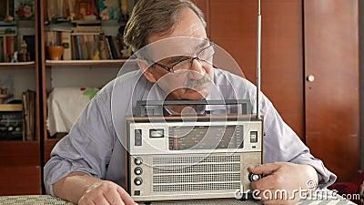 Пожилой человек с усиком поворачивает дальше винтажное радио и слушает к музыке Вытягивает вне антенну, включает кнопка акции видеоматериалы