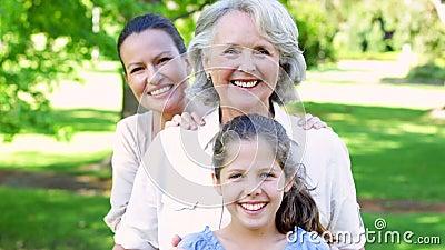 3 поколения женщин усмехаясь на камере в парке видеоматериал
