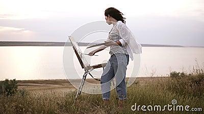 Полнометражный отснятый видеоматериал красивой девушки в белой рубашке и джинсах работая outdoors Краски используя мольберт и кра акции видеоматериалы