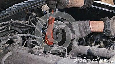 Попытка механика автомобиля для того чтобы сделать быстрый ремонт автомобиля с осью outdoors Все пакостно сток-видео