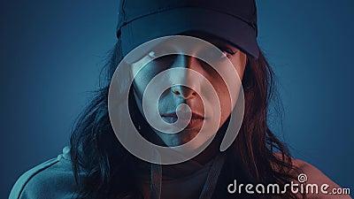 Портрет девушки в кэп смотрит на камеру в цветном фильтре Многоцветные цвета в неоновом освещении темной комнаты Молодая женщина акции видеоматериалы