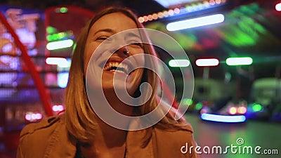 Портрет женщины смотря камеру и смеясь над в парке атракционов акции видеоматериалы