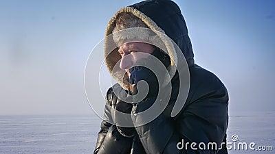 Портрет конца-вверх замороженного бизнесмена в клобуке говоря многодельно на мобильном телефоне в пустыне снега видеоматериал