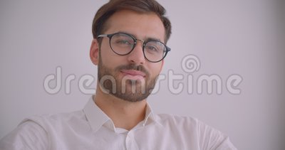 Портрет крупного плана взрослого красивого бородатого кавказского бизнесмена в стеклах смотря камеру усмехаясь жизнерадостно сидя сток-видео