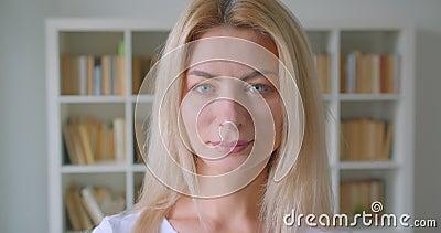 Портрет крупного плана взрослой кавказской белокурой женщины смотря камеру усмехаясь жизнерадостно внутри помещения в библиотеке  видеоматериал