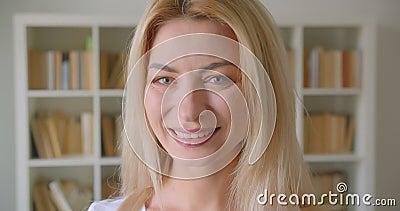 Портрет крупного плана взрослой кавказской белокурой женщины смотря камеру усмехаясь жизнерадостно внутри помещения в библиотеке сток-видео