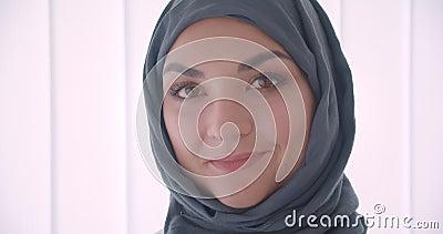 Портрет крупного плана молодой мусульманской привлекательной коммерсантки в hijab смотря камеру усмехаясь жизнерадостно в белизне видеоматериал