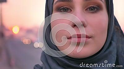 Портрет крупного плана молодой привлекательной мусульманской женщины в стороне hijab смотря уверенно на камере с городским городо сток-видео