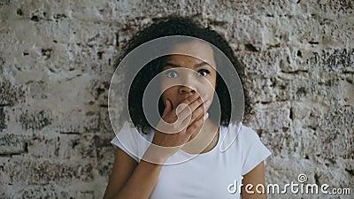 Портрет курчавый смешанной гонки женщины смотреть активно удивительно и интересуя в камеру на предпосылке кирпичной стены сток-видео
