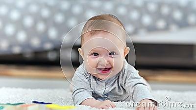 Портрет лежать прелестного маленького милого младенца усмехаясь на пушистом ковре дома смотря камеру сток-видео