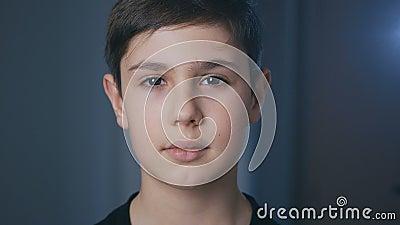 Портрет милого мальчика 11 лет, который смотрит на камеру дома вечером акции видеоматериалы