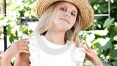 Портрет милой девушки в соломенной шляпе усмехаясь, касающся ее волосам и шляпе конец вверх lifestyle принципиальная схема детств сток-видео