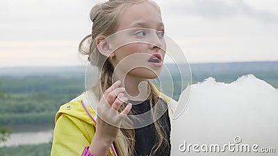 Портрет предназначенной для подростков девушки ест сладкий хлопок идя на парк города акции видеоматериалы