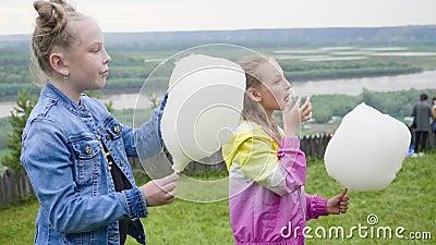 Портрет предназначенных для подростков девушек ест сладкий хлопок идя на природный парк акции видеоматериалы
