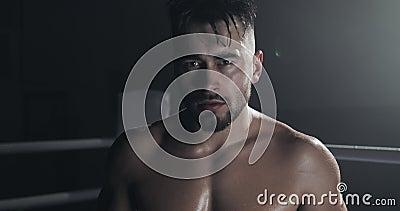 Портрет сердитого мужского положения боксера на боксерском ринге и смотреть интенсивно на камере видеоматериал