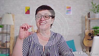 Портрет слух-поврежденной усмехаясь женщины держа слуховой аппарат сидя в живущей комнате сток-видео