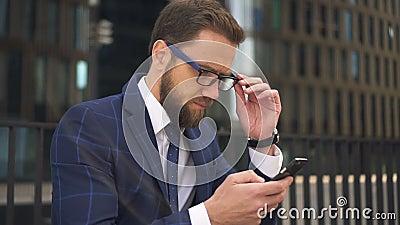 Портрет успешного бизнесмена использует smartphone на предпосылке здания города сток-видео