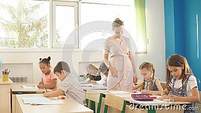 Порция учителя ягнится с их домашней работой в классе на школе сток-видео